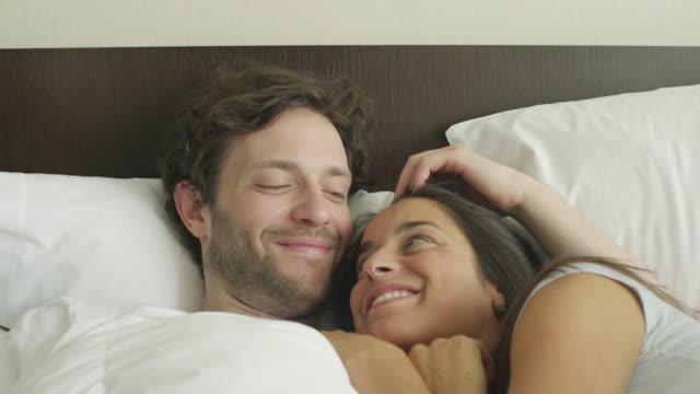 coupld embracing in bed - auf dem rücken liegen stock-videos und b-roll-filmmaterial