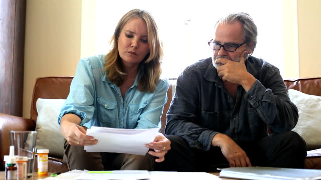 couple add up medical bills warily - medical insurance stock videos & royalty-free footage