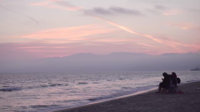 vídeos de stock e filmes b-roll de couple admires sunset on venice beach, wide - cadeira