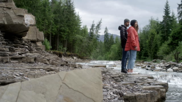 Couple admiring the view. Mountain landscape with river
