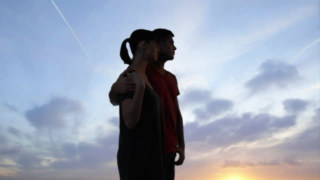 couple against dramatic sunrise - coda di cavallo video stock e b–roll