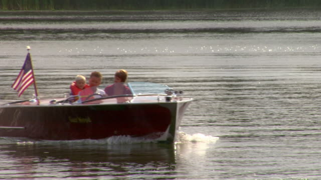 A couple and a boy ride in a wooden motorboat on Pelican Lake in Pelican Rapids, Minnesota.