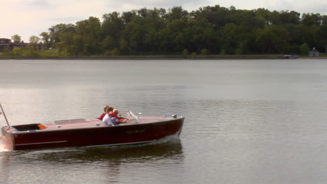 A couple and a boy ride in a wooden motorboats on Pelican Lake in Pelican Rapids, Minnesota.