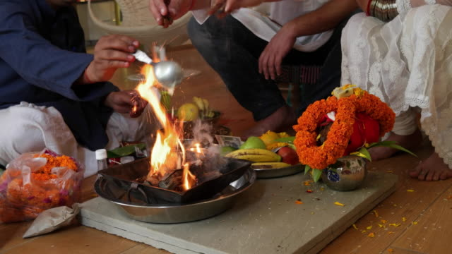 a couple and a priest performing a havan or home puja in a hindu household, around a fire lit in houour of deity agni, with religious offerings - cerimonia tradizionale video stock e b–roll