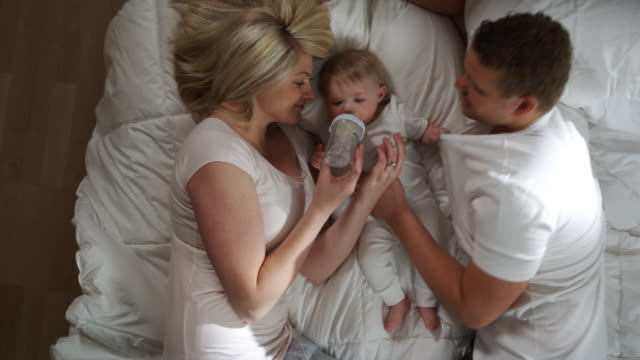 stockvideo's en b-roll-footage met couple and baby in bed - zuigfles