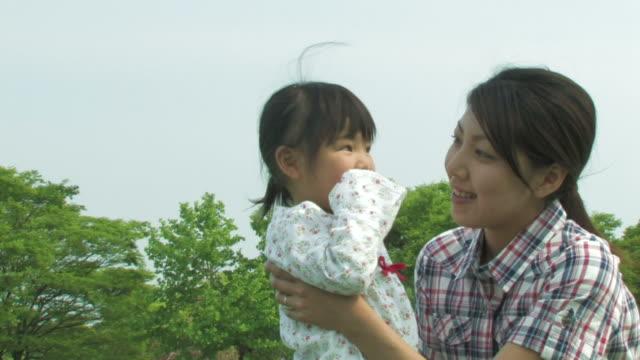 pan couple and daughter playing in park - förälder och barn bildbanksvideor och videomaterial från bakom kulisserna