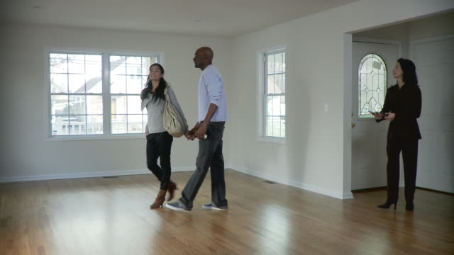 ws, pan, couple and female real estate agent in empty room, plainfield, new jersey, usa - ganzkörperansicht stock-videos und b-roll-filmmaterial