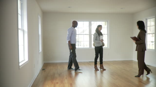 ws, pan, couple and female real estate agent in empty room, plainfield, new jersey, usa - 住宅購入点の映像素材/bロール
