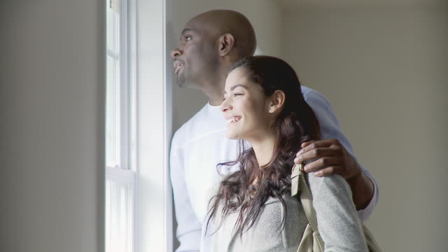MS, PAN, Couple and female real estate agent looking through window in empty room, Plainfield, New Jersey, USA