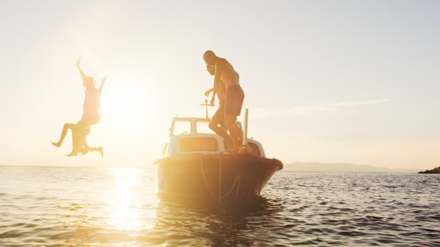 slo mo couple and their friends jumping off a boat at sunset - barca a motore video stock e b–roll