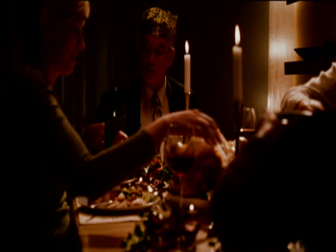 couple and their parents eating christmas dinner together around a candlelit table in their dining room - brühe stock-videos und b-roll-filmmaterial