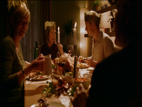 couple and their parents eating christmas dinner together around a candlelit table in their dining room - adult offspring stock videos & royalty-free footage