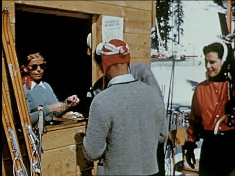 / couple approaches ski lift carrying skis, buys lift tickets, locking boots into ski bindings, riding ski lift. - 1954年点の映像素材/bロール