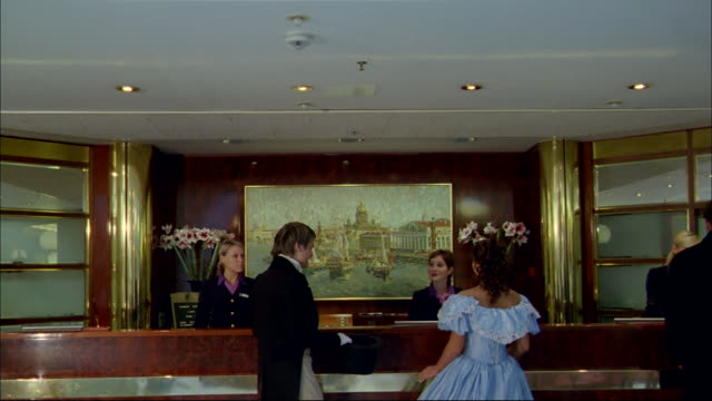 vidéos et rushes de a couple approaches the counter of a luxurious hotel. - palace