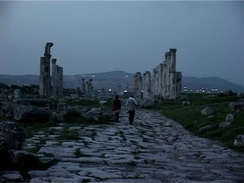 couple are walking away from the camera towards the roman great colonnade at sunset at the archaeological site of apamea. - roman stock videos & royalty-free footage