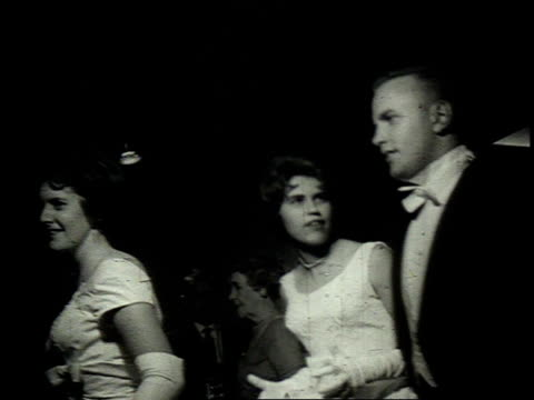 1962 montage couple arriving at a debutante ball / united states - 舞踏会点の映像素材/bロール