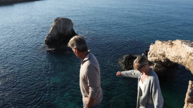 couple ascend coastal rocks above natural bridge - gemeinsam gehen stock-videos und b-roll-filmmaterial
