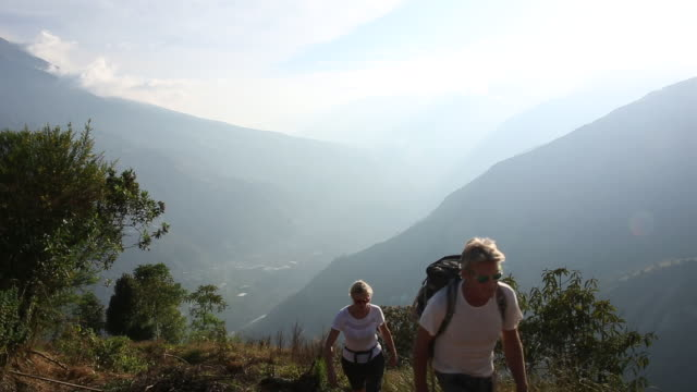 couple ascend mountain path, above valley - pedal pushers stock videos & royalty-free footage