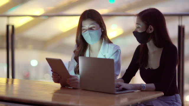 couple asian business women wear face mask working late at night with laptop at office - working overtime stock videos & royalty-free footage