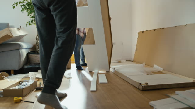 vídeos de stock e filmes b-roll de slo mo couple assembling a new furniture at home - mobília