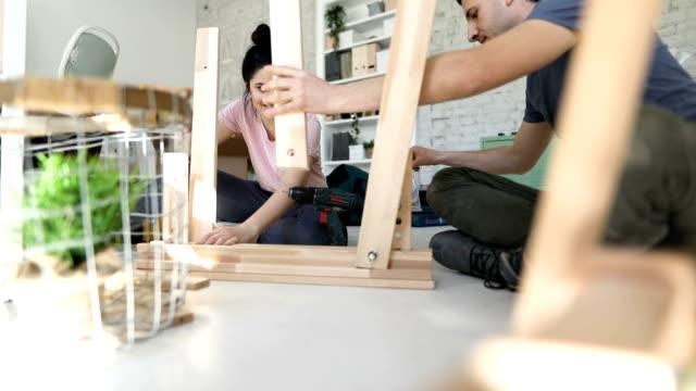 vídeos y material grabado en eventos de stock de pareja de montaje de muebles juntos - muebles