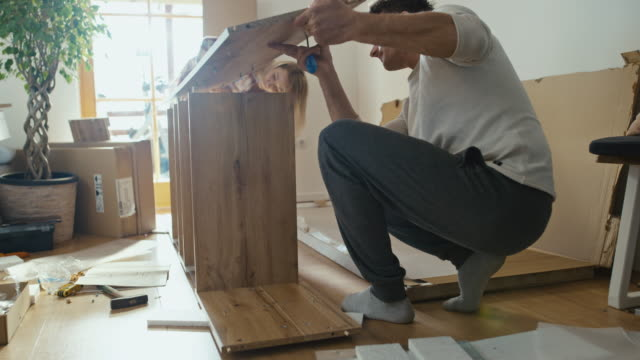slo mo couple assembling the furniture at home - work tool stock videos & royalty-free footage