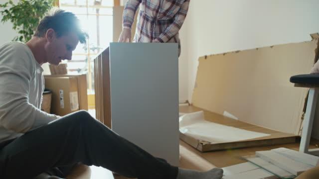 vídeos y material grabado en eventos de stock de slo mo couple ensamblar los muebles en casa - reforma
