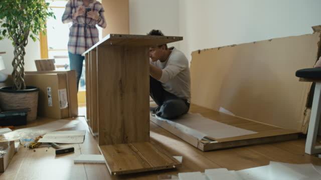 vídeos y material grabado en eventos de stock de timelapse pareja montando los muebles en casa - montar