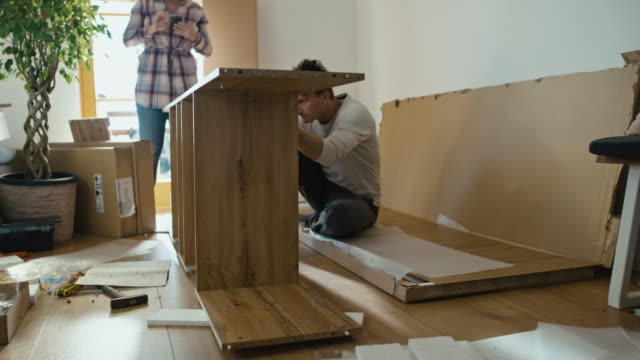 vídeos de stock e filmes b-roll de timelapse couple assembling the furniture at home - prateleira mobília