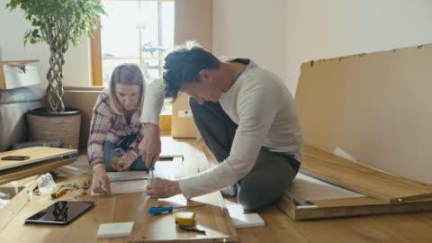 vídeos y material grabado en eventos de stock de slo mo pareja montaje de los muebles - estante muebles