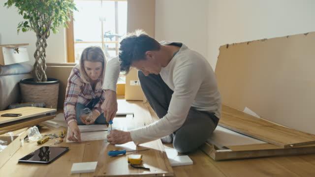 vídeos de stock e filmes b-roll de slo mo couple assembling the furniture - prateleira mobília