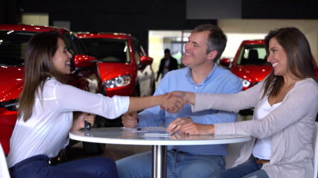 vídeos de stock e filmes b-roll de couple at a dealership closing a deal to with a saleswoman - stand de carros