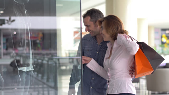 couple at a mall looking to a window store and pointing the outfit - spending money stock videos & royalty-free footage