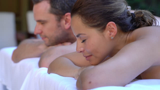Couple at a spa getting a back massage and looking relaxed