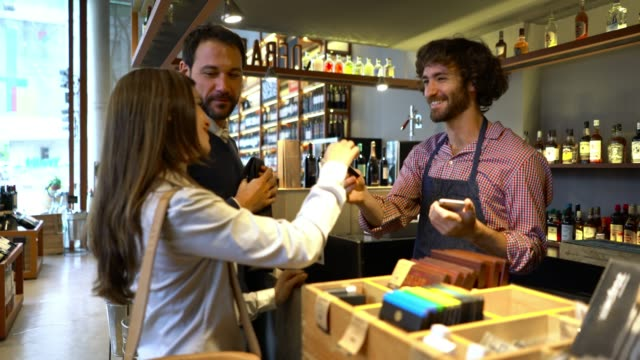 couple at a wine store paying with credit card and sales clerk processing payment with a smartphone - argentina stock videos & royalty-free footage