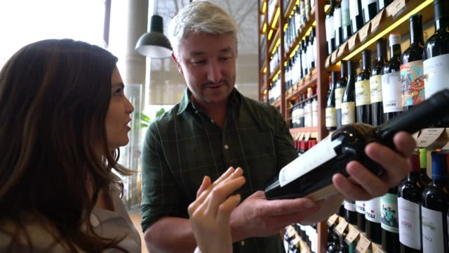 Couple at a winery choosing wines and woman giving her opinion about the taste