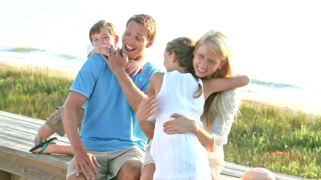 paar am strand umarmung kinder über gefordert - heranlocken stock-videos und b-roll-filmmaterial