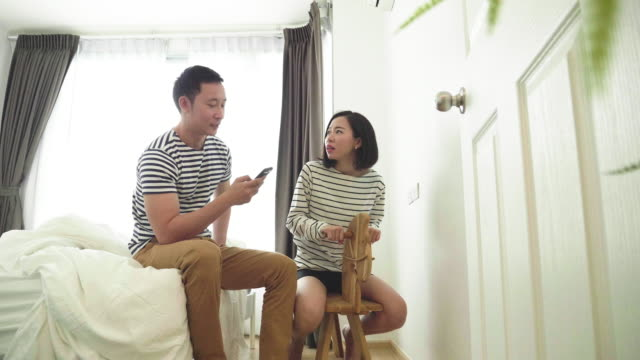 Couple at bedroom talking while using smart phone - Stock video