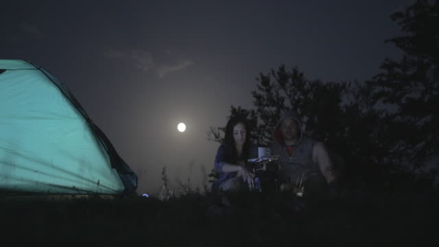 Couple at camping with a tent and moon light