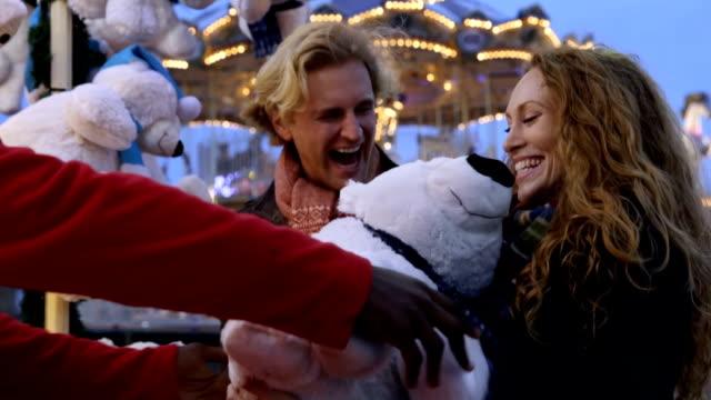zu zweit am weihnachtsmarkt spielzeuge zu gewinnen - real wife sharing stock-videos und b-roll-filmmaterial