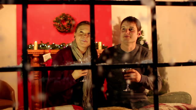 Couple at Christmas window drinking mulled wine