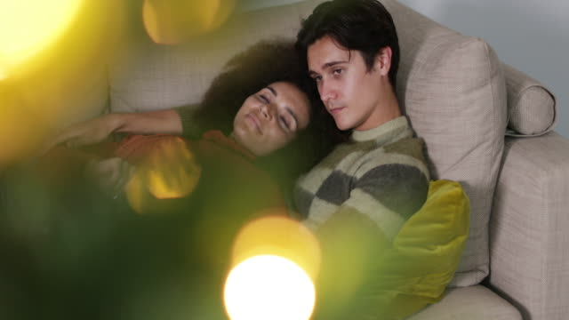 Couple at home cuddling on sofa at Christmas