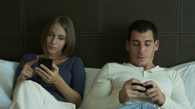 4K: Couple at home in bed late using mobile phone in relationship communication problem and internet social media network concept