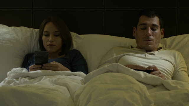 4k: couple at home in the bed late at night using mobile phone in relationship communication problem and internet social media network concept. - bedtime stock videos & royalty-free footage