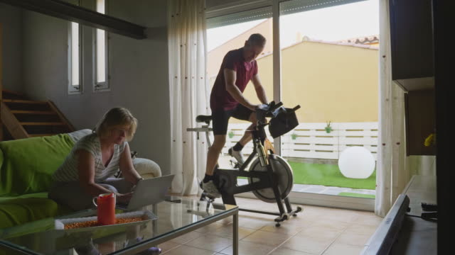 couple at home on an everyday routine during the pandemic - exercise bike stock videos & royalty-free footage