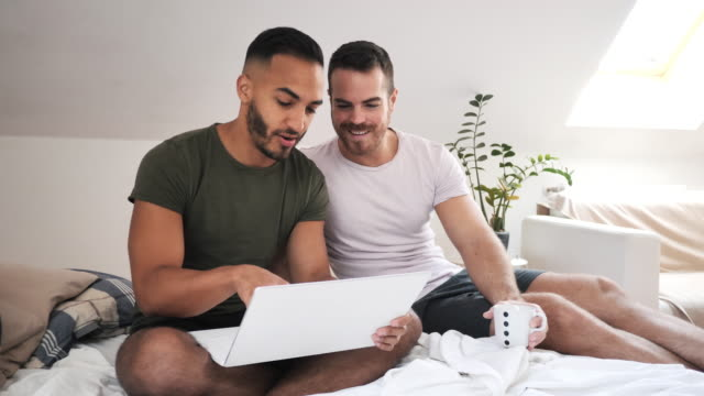 lgbt couple at home using internet and laptop to chat with friends - online shopping stock videos & royalty-free footage