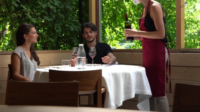 vidéos et rushes de couples à la table de restaurant, serveuse servant le vin rouge - verre à vin