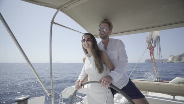 couple at steering wheel of boat
