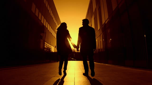 hd slow-motion: couple at sunset - back lit woman stock videos & royalty-free footage