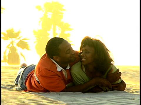 vídeos de stock e filmes b-roll de couple at the beach - encostado